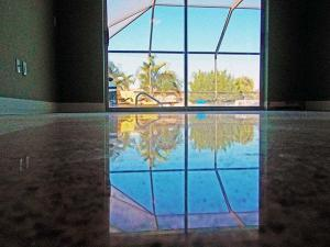 Reflection of pool cage in terrazzo in Marco Island